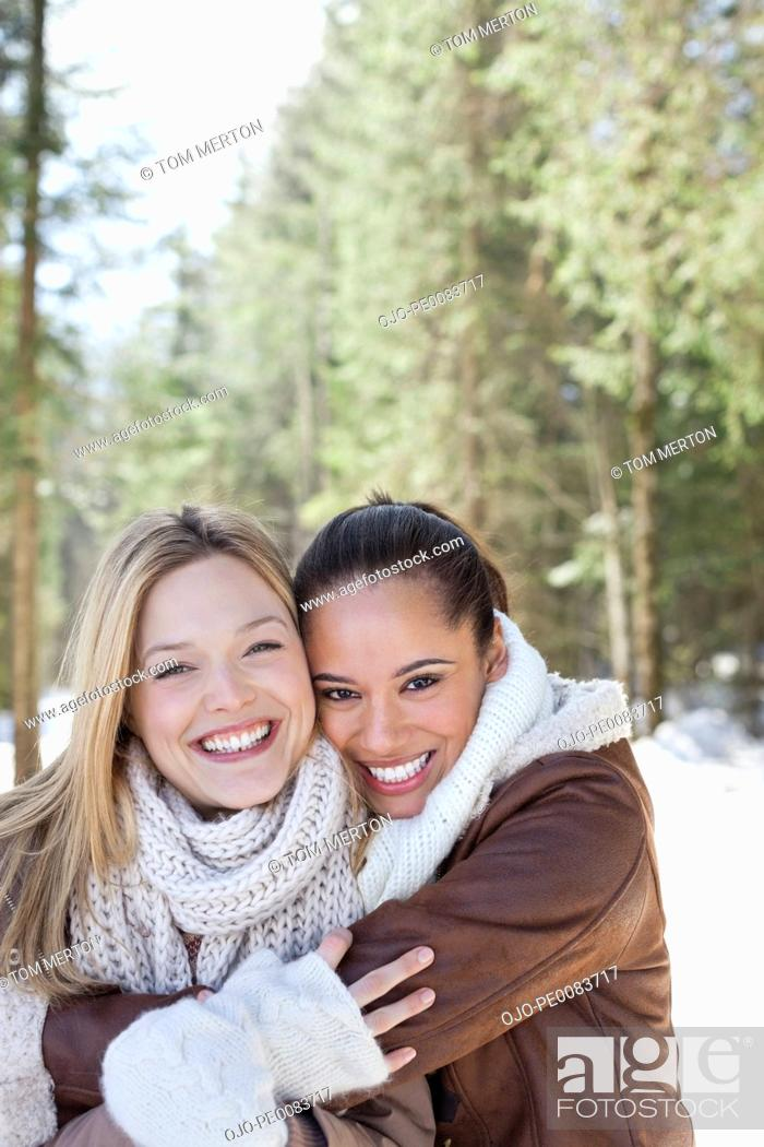 Stock Photo: Portrait of smiling friends hugging in snowy woods.