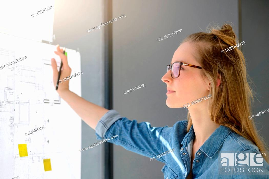 Stock Photo: Woman contemplating plans on glass wall.