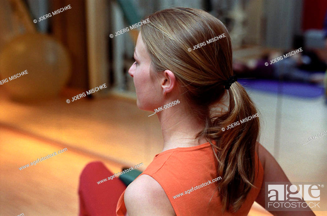 Stock Photo: Young woman at the gym, fitness center, doing some exercise.