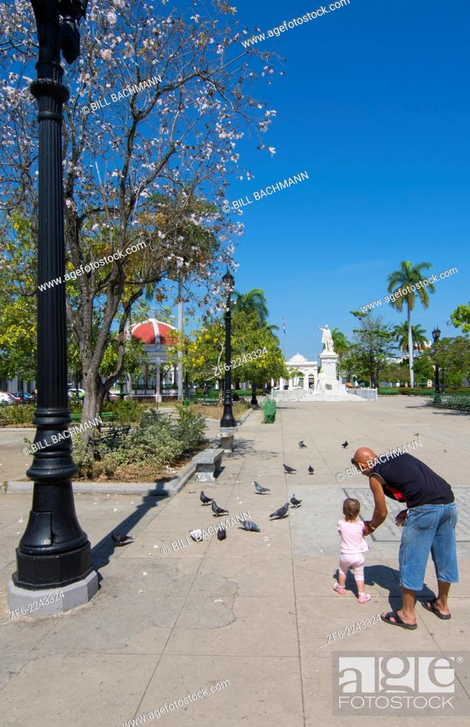 Stock Photo: Cienfuegos Cuba center square in city center with girl and Dad feeding birds 9.