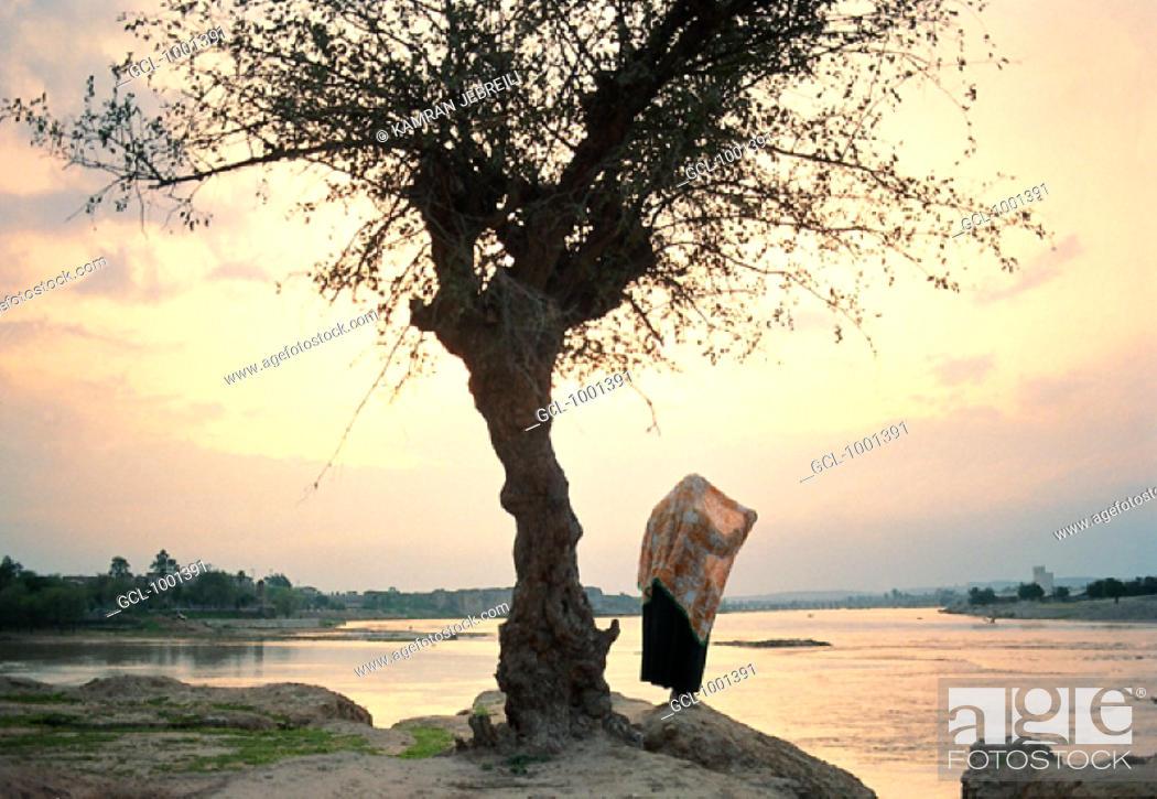 Stock Photo: Woman standing at Dez river in Khuzestan, Iran.