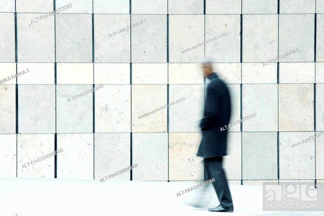 Stock Photo: Man walking on sidewalk.