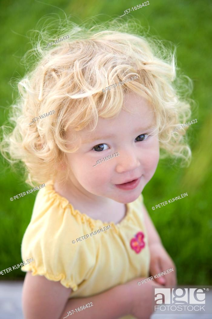 Stock Photo: Portrait of a young girl with curly blond hair looking into the camera looking mischeivious.