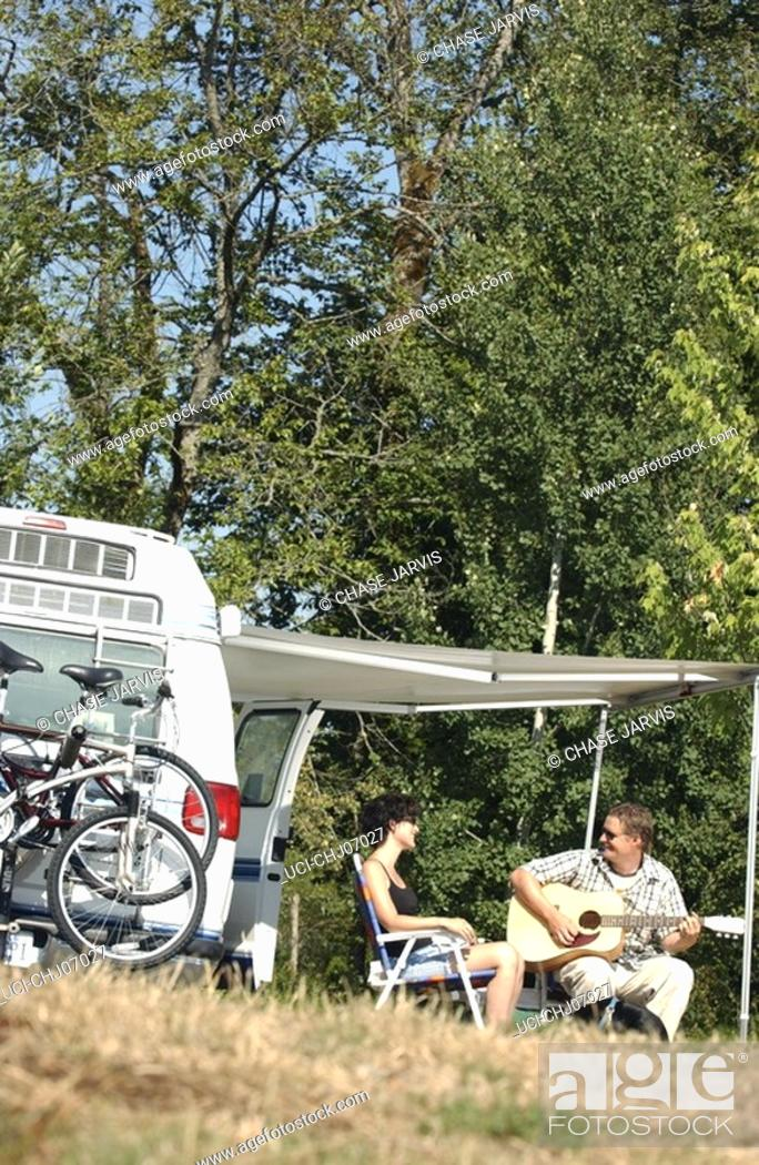 Imagen: Couple camping and playing guitar.