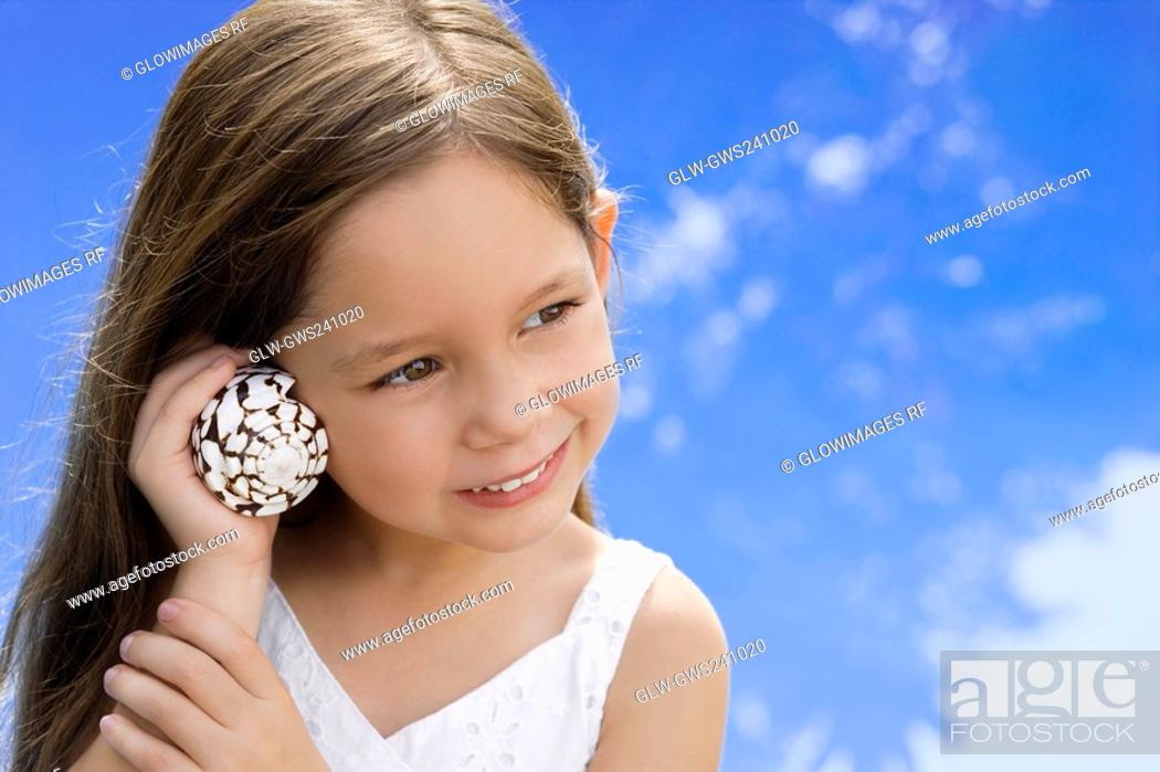 Stock Photo: Close-up of a girl listening to shell and smiling.