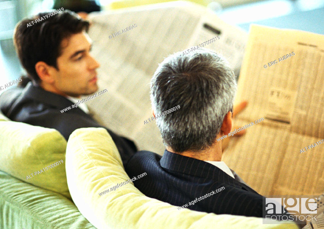 Stock Photo: Businessmen sitting reading newspapers, rear view, head and shoulders.