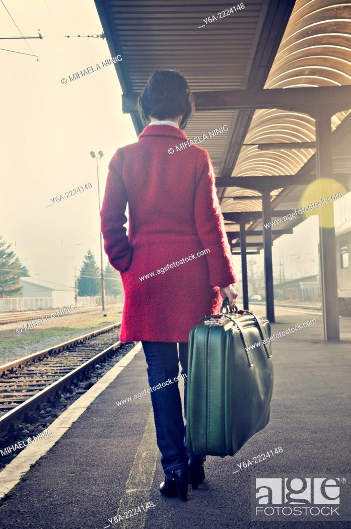Stock Photo: Woman carrying suitcase standing on railroad station platform, rear view.
