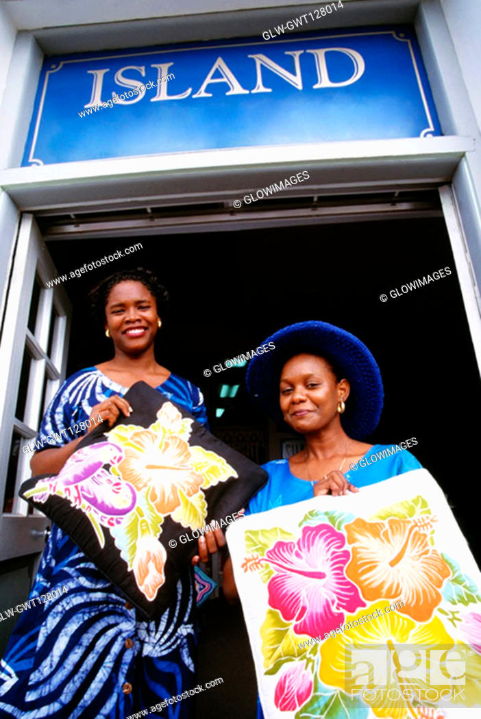 Stock Photo: Low angle view of two women smiling at the camera, St. Kitts.
