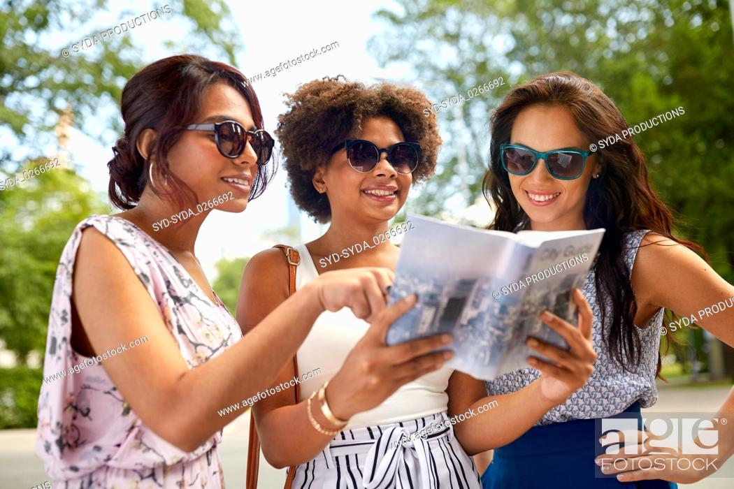 Photo de stock: happy women with city guide on street in summer.