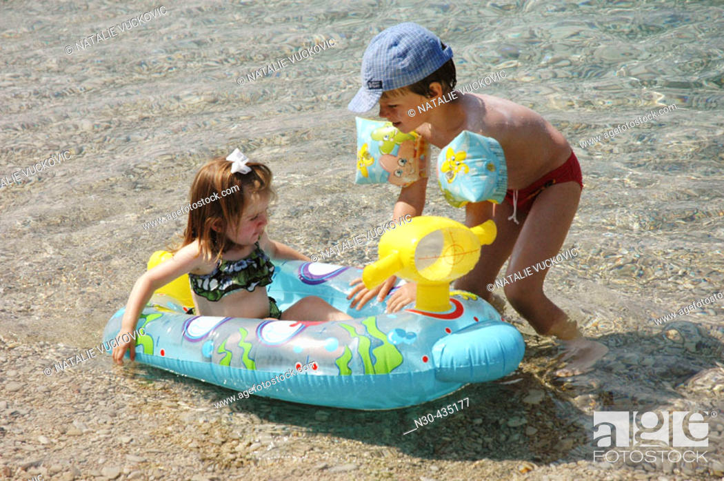 Stock Photo: Toddler boy playing with toddler girl at beach.
