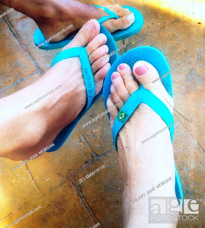 Stock Photo: Three feet wearing blue flip-flops.