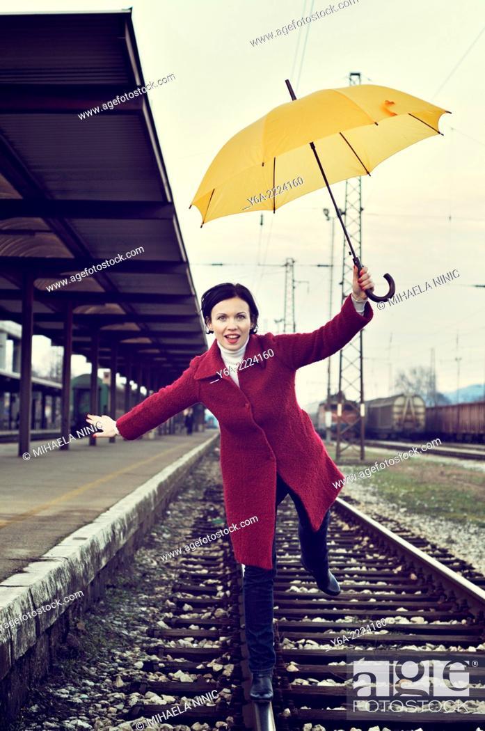 Stock Photo: Woman balancing on one leg standing on railway track holding umbrella.