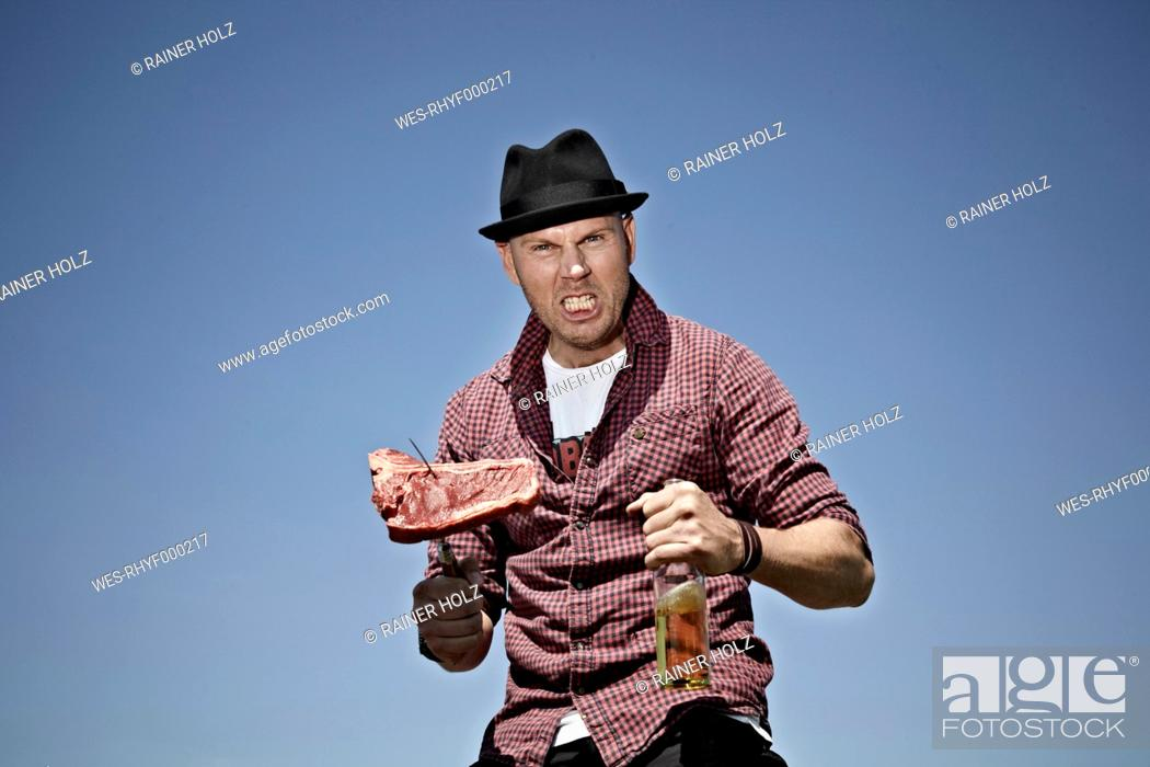 Stock Photo: Germany, Cologne, Mature man with meat and beer.