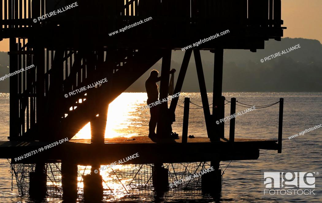 Stock Photo: 31 July 2020, Bavaria, Utting: An early bathing guest stands in the sunrise on the footbridge of a beach bath under a wooden diving tower.
