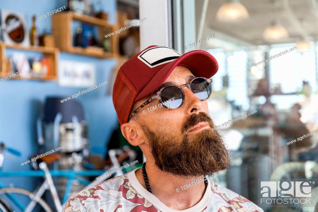 Stock Photo: Matue man with red basecap and sunglasses.