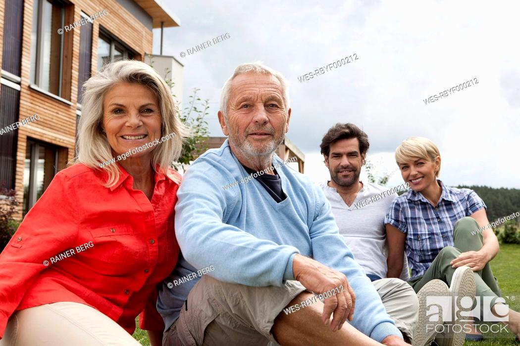 Stock Photo: Germany, Bavaria, Nuremberg, Portrait of family sitting in front of house.