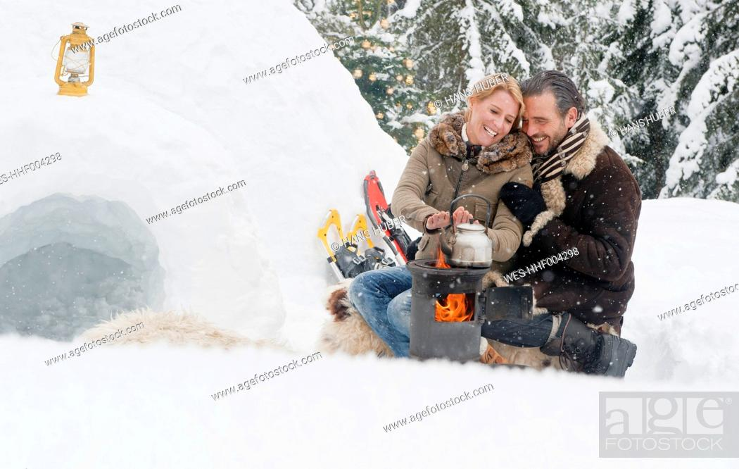 Stock Photo: Austria, Salzburg County, Couple sitting near fireplace, smiling.