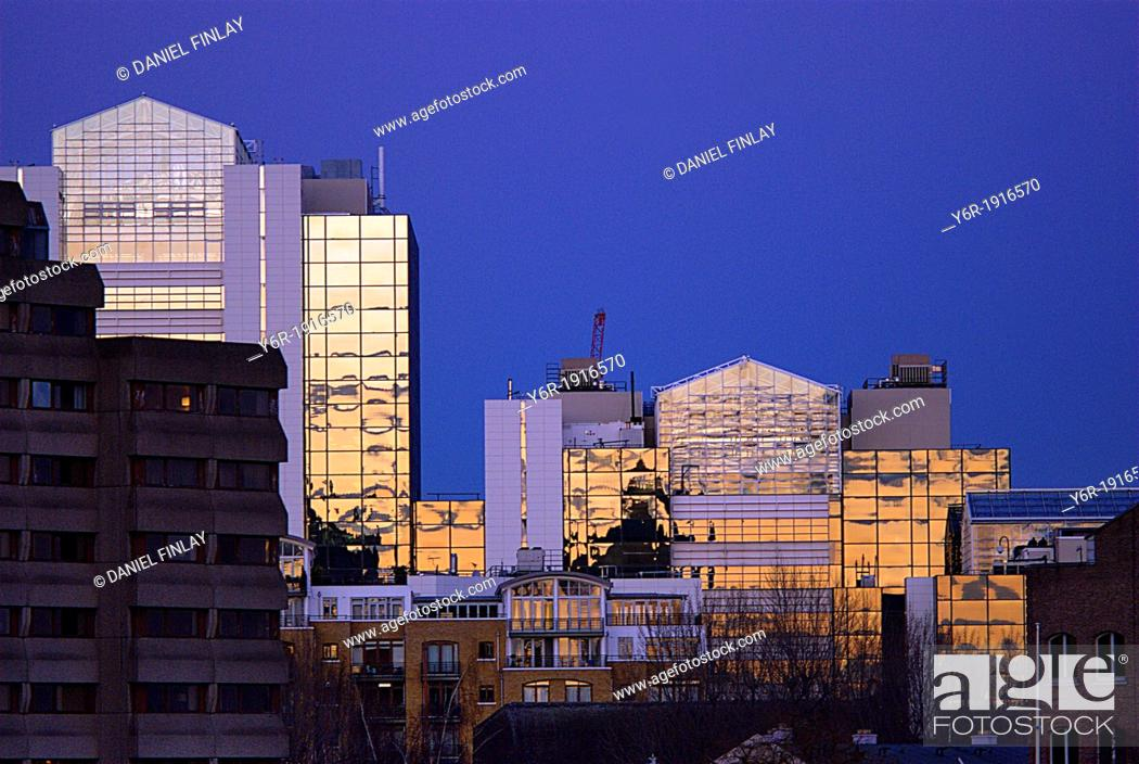 Stock Photo: East London office buildings seen from Tower Bridge lit up by a bright sunset in the capital of England.