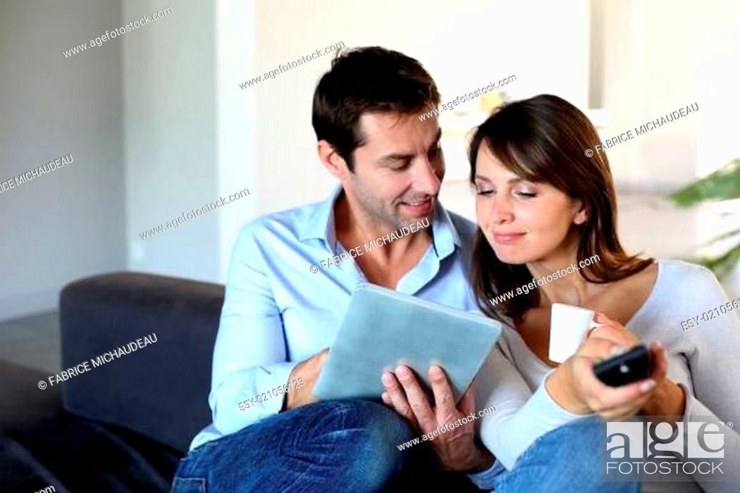 Stock Photo: Couple sitting in couch choosing tv program.