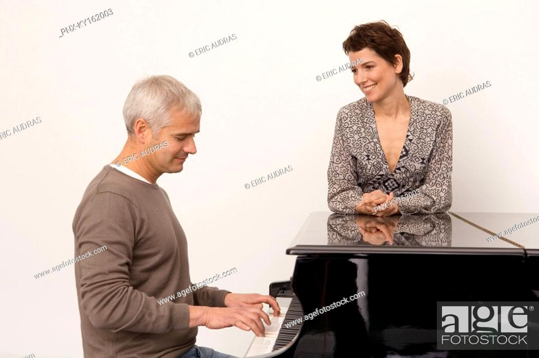 Stock Photo: Mature man playing a piano and a mid adult woman standing near him.