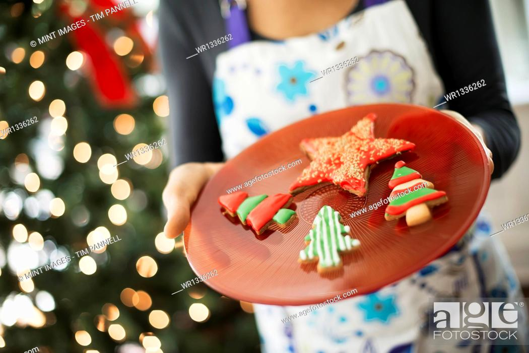 Stock Photo: A woman wearing an apron holding a plate of organic decorated Christmas cookies.