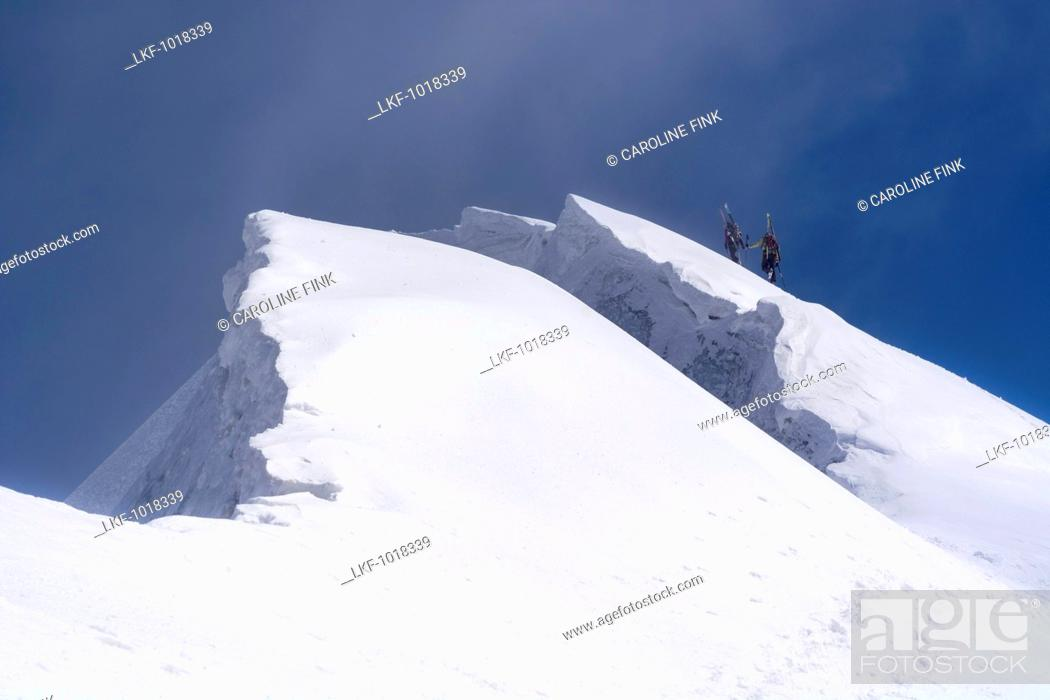 Stock Photo: A female and a male mountaineer carrying their touring skis on their backpacks and ascending a steep snow slope, next to them big snow cornices.