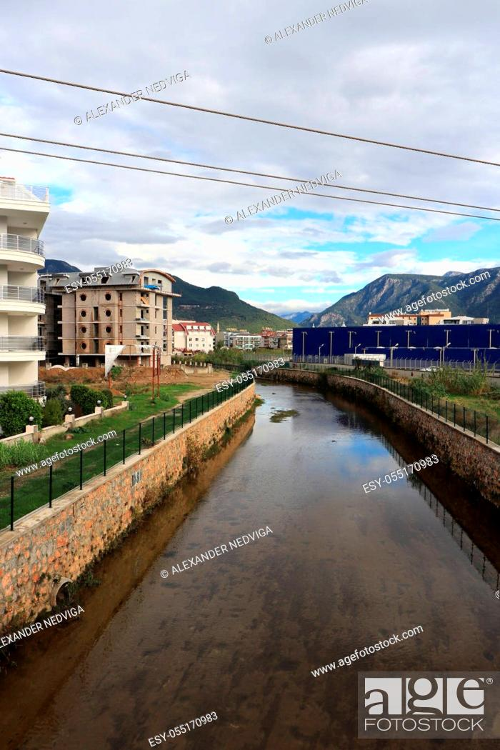 Stock Photo: Old river channel descending from the mountains. New buildings are under construction.