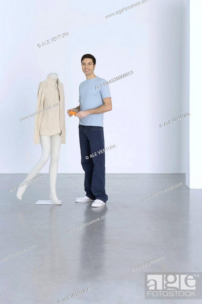 Stock Photo: Man standing beside sweater on mannequin, holding price tag, smiling at camera.