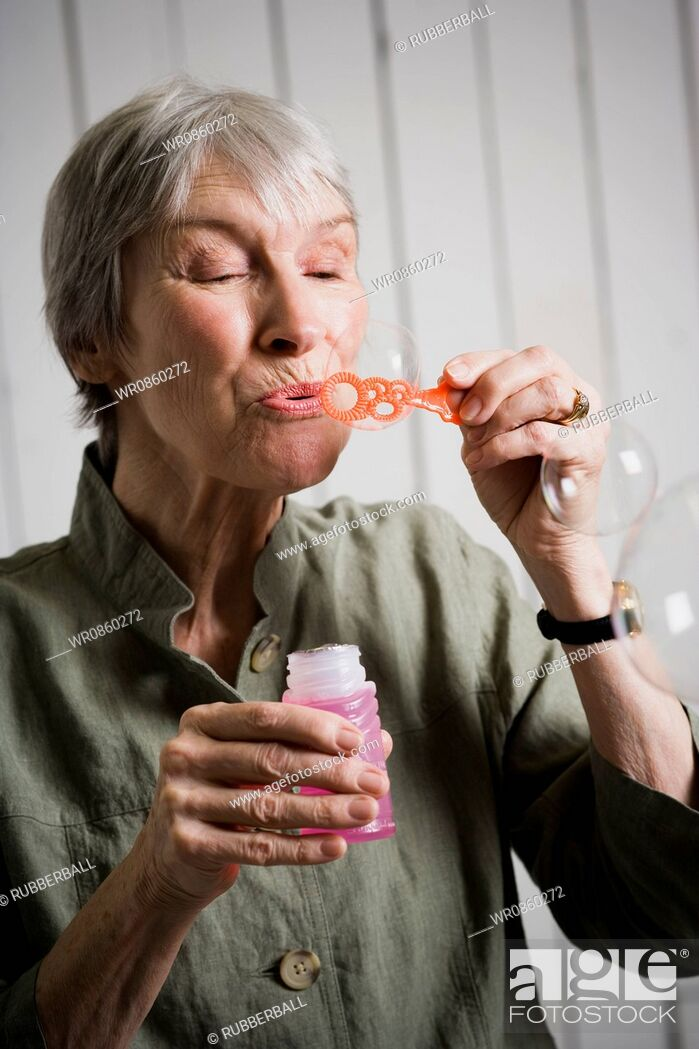 Stock Photo: Portrait of an elderly woman blowing bubbles with a bubble wand.