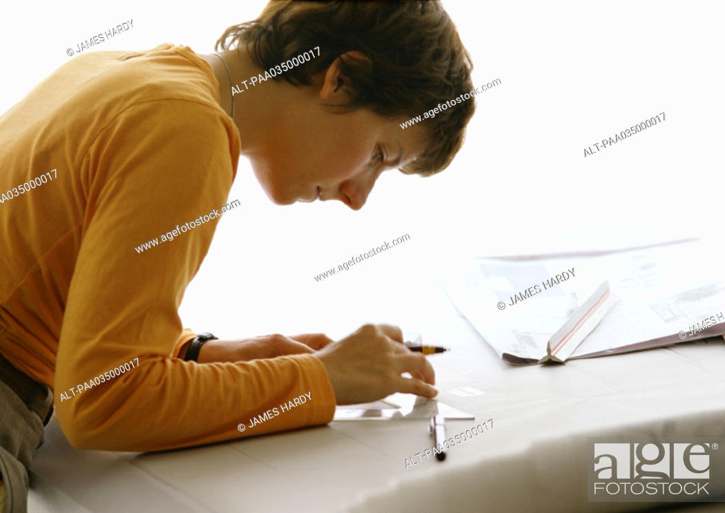 Stock Photo: Woman bending over table, holding set square and pen, side view.
