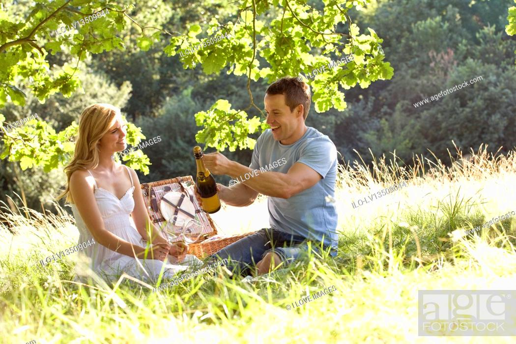 Stock Photo: A young couple having a picnic, man opening a bottle of sparkling wine.