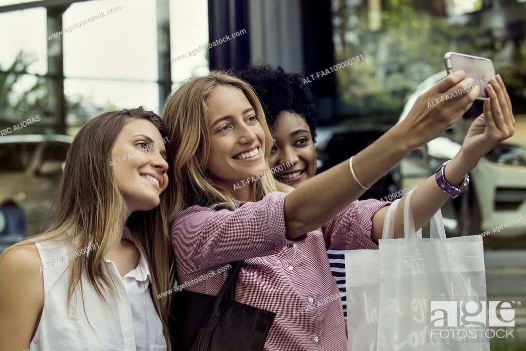 Stock Photo: Friends using smartphone to take a selfie while out shopping.