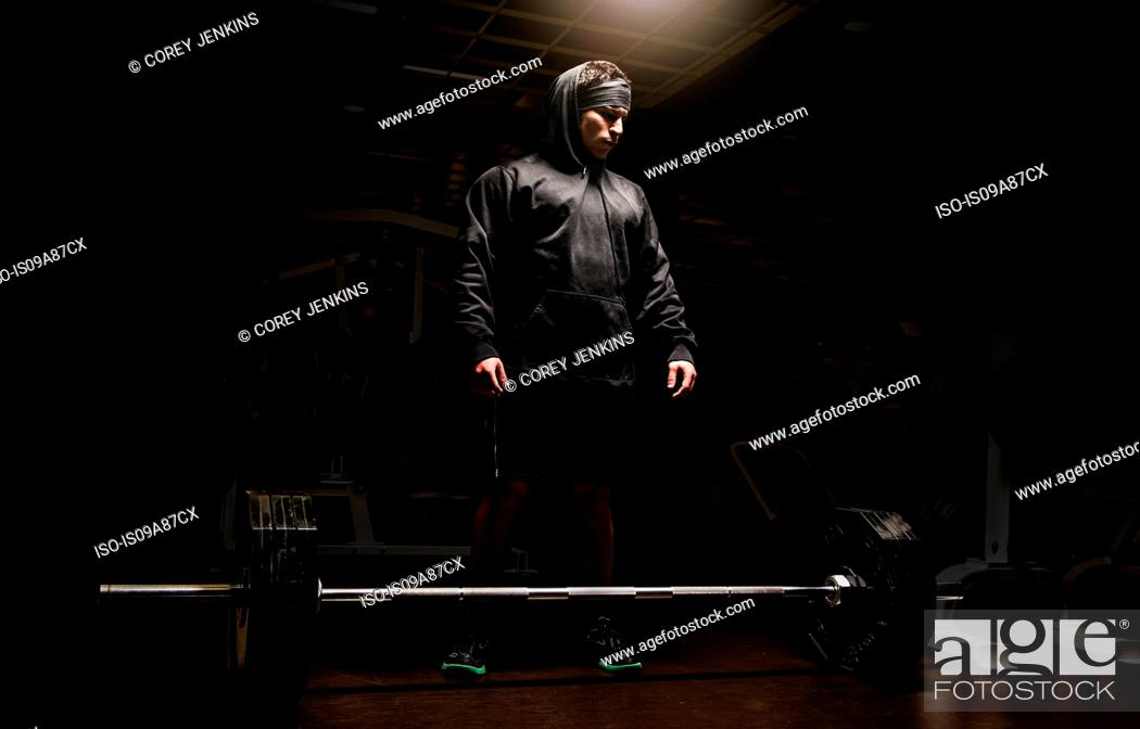 Stock Photo: Young man preparing to lift barbell in gym.
