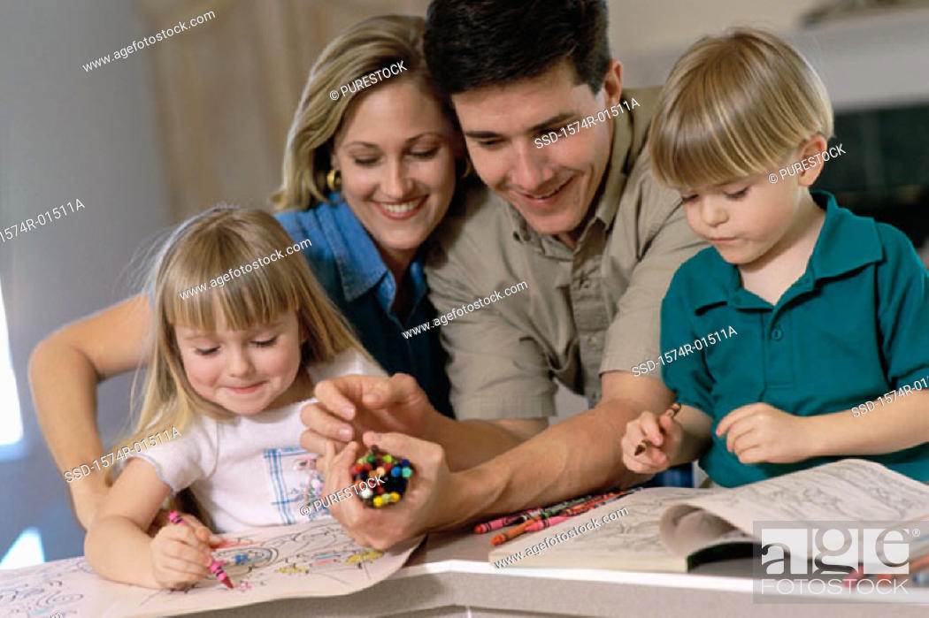 Stock Photo: Parents and their children drawing in a coloring book.