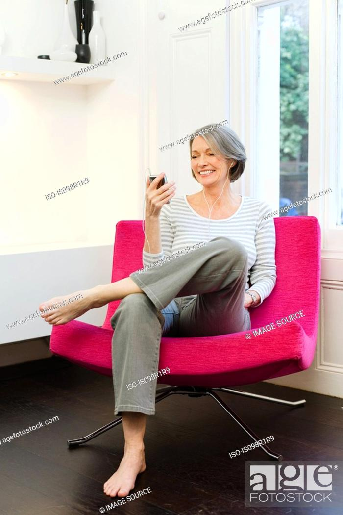 Stock Photo: Mature woman listening to mp3 player.