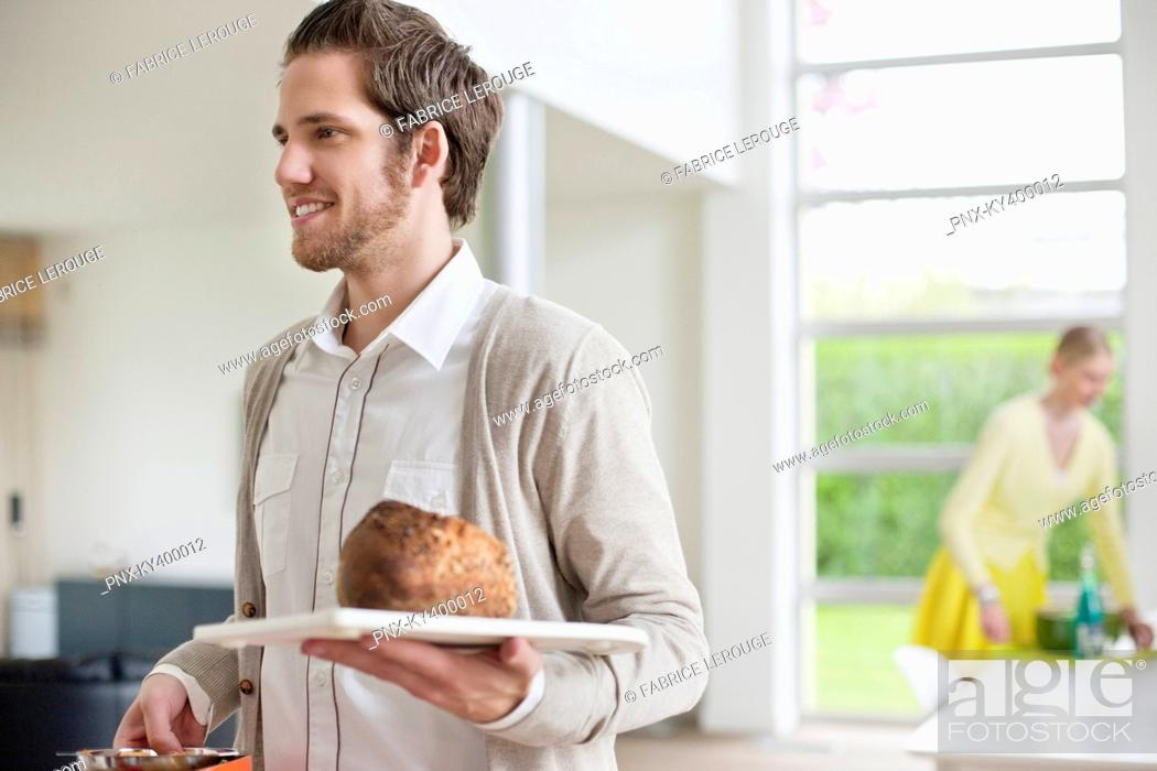 Stock Photo: Man carrying bread on a tray.