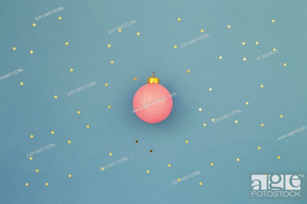 Stock Photo: Pink Christmas ball on blue holiday background with gold stars sequins. Minimal New Year greeting card. Shining Night sky at christmas concept.