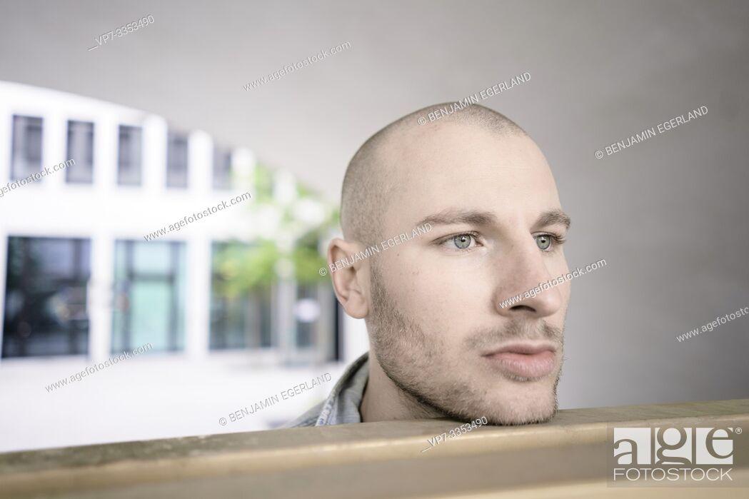 Stock Photo: headshot of man musing in city.