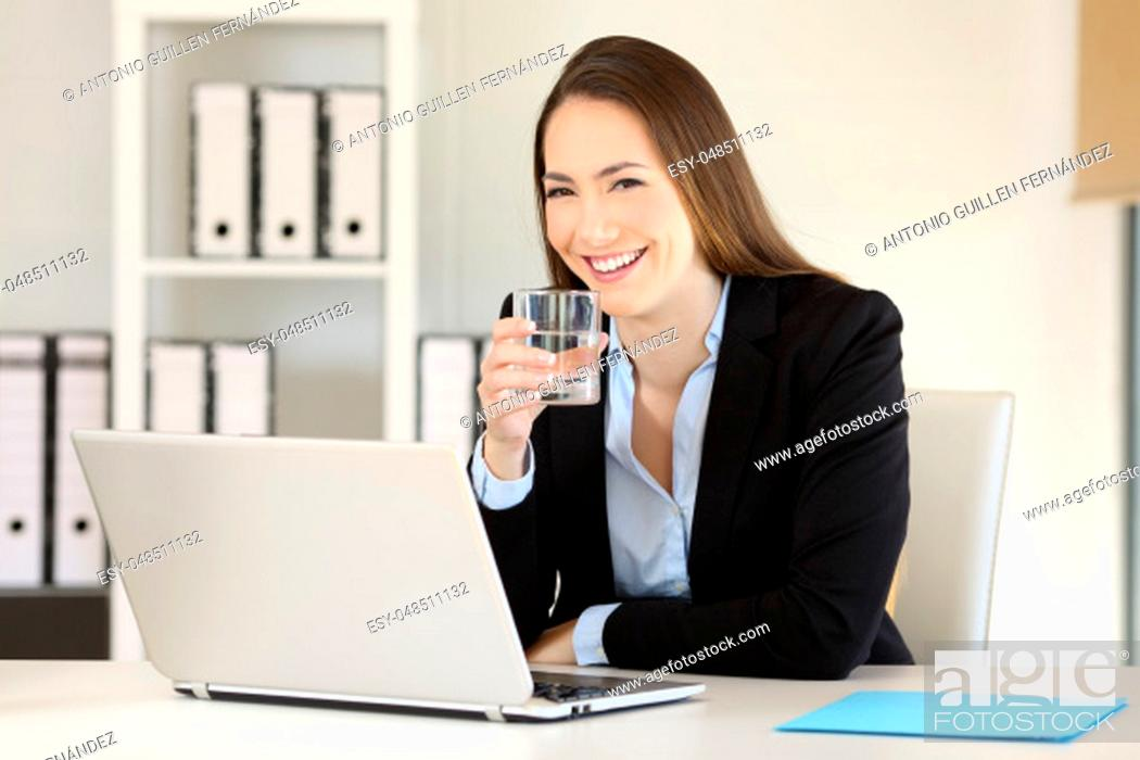 Stock Photo: Happy executive holding a glass of water and looking at camera at office.