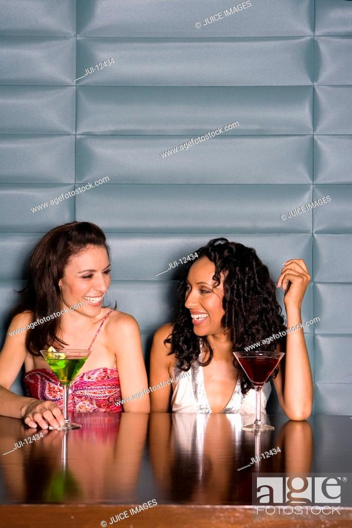 Stock Photo: Young woman at table with cocktail, smiling at friend.