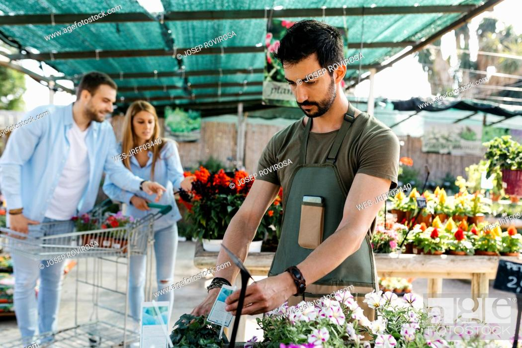 Stock Photo: Worker in a garden center placing labels on flowers with customers in background.