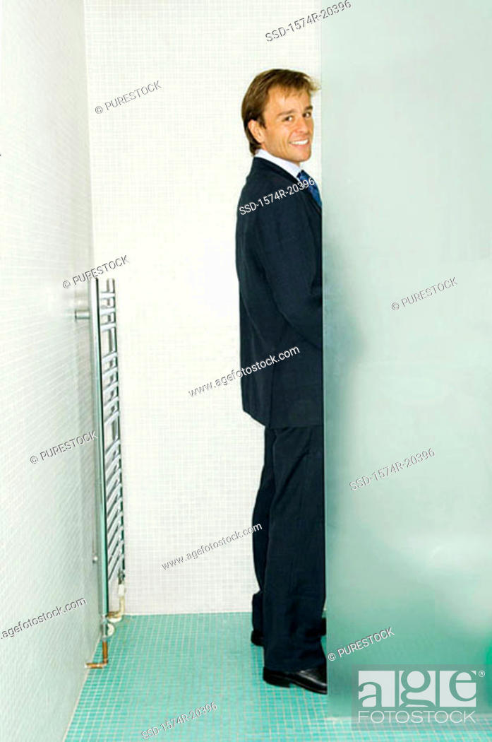 Stock Photo: Portrait of a businessman standing in a public restroom.