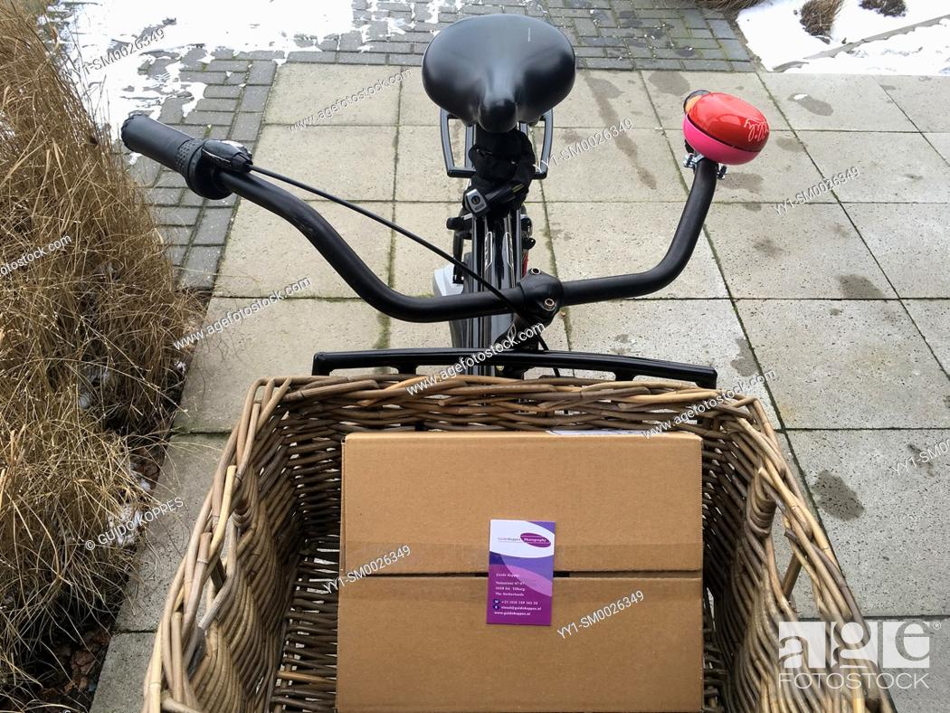 Imagen: Tilburg, Netherlands. Sturdy, Dutch Transport bicycle, carrying a boxed cargo of new, fresh business cards.
