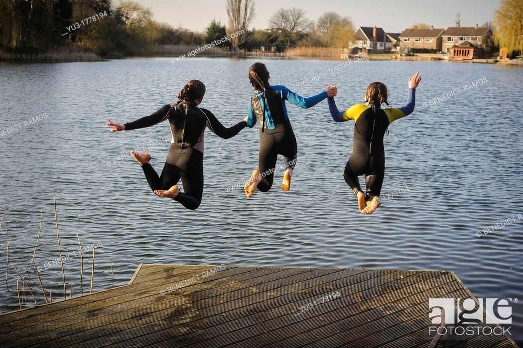 Stock Photo: Three girls jumping into a lake while holding hands, England, UK.
