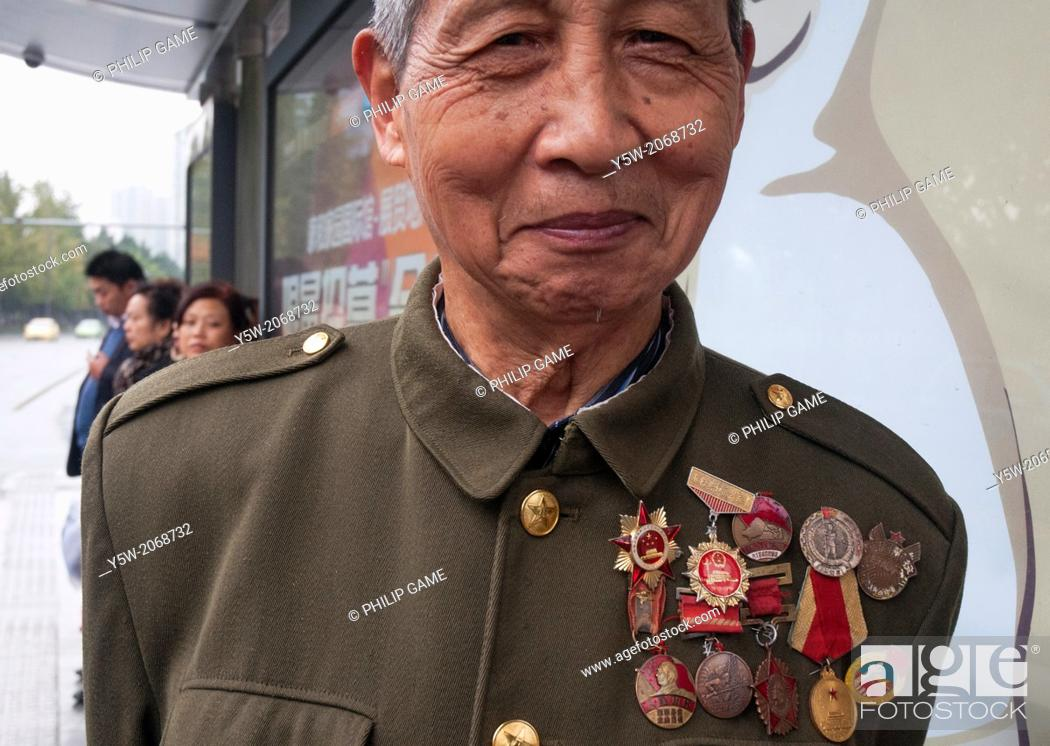 Stock Photo: Elderly eccentic in Chengdu shows off his collection of Mao-era medals and badges.