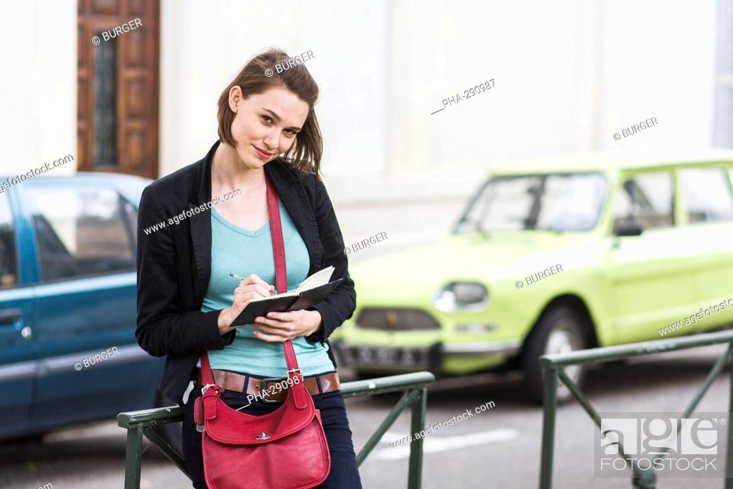Stock Photo: Woman writing in a notebook.