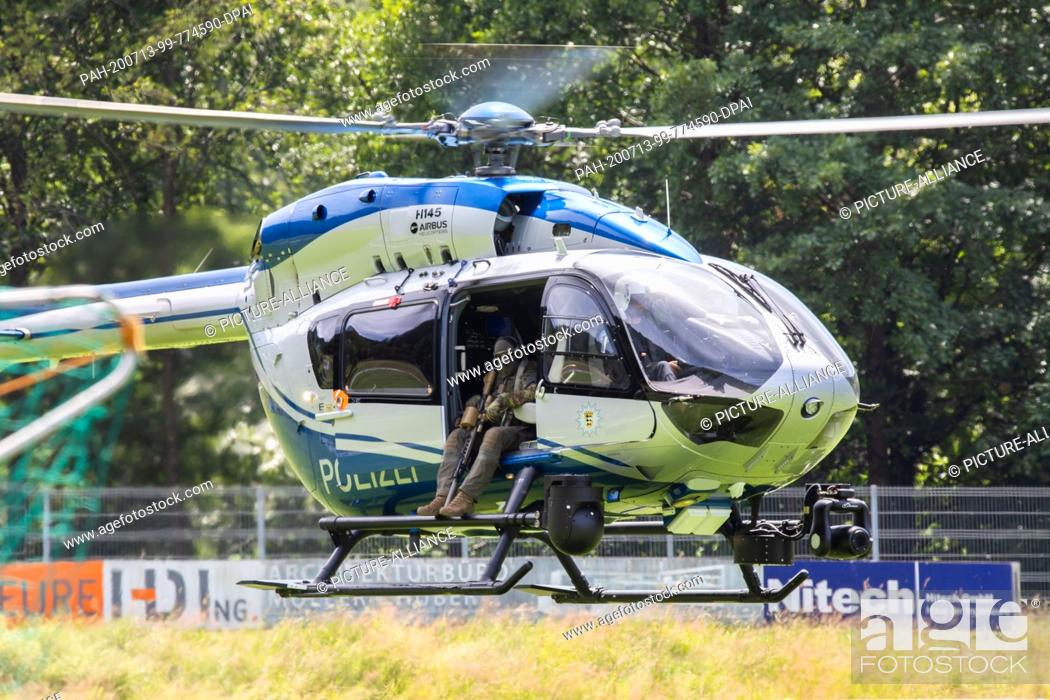 Stock Photo: 13 July 2020, Baden-Wuerttemberg, Oppenau: A police helicopter lands near the community of Oppenau on a sports field, which serves as a meeting point for the.