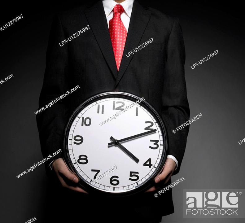 Stock Photo: Businessman Holding Clock.