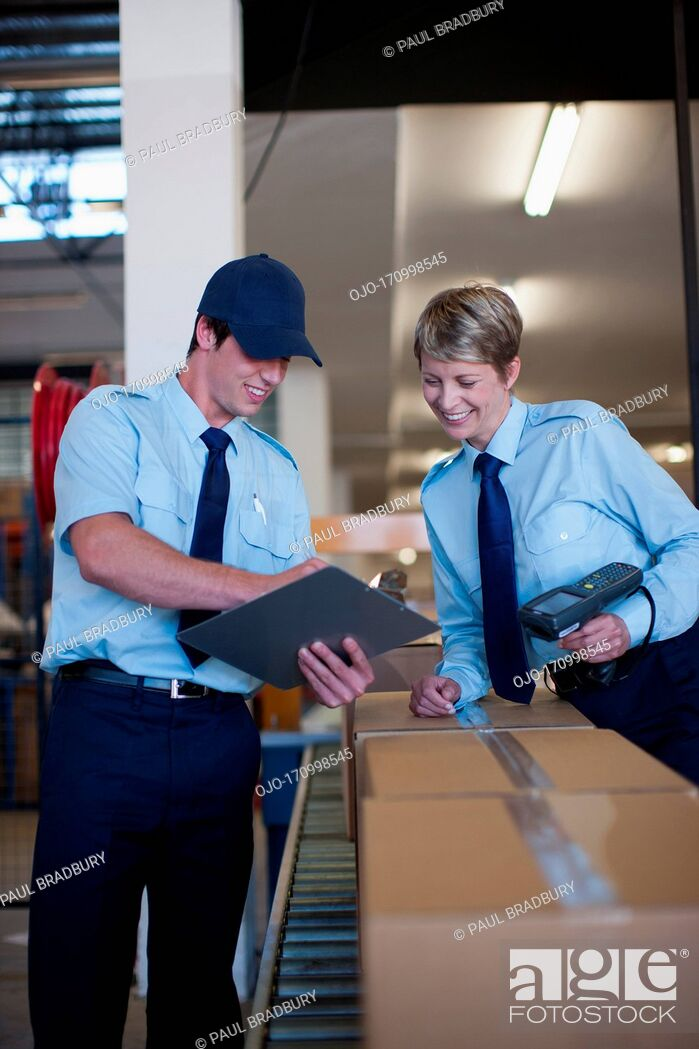 Stock Photo: Workers standing together near box on conveyor belt.