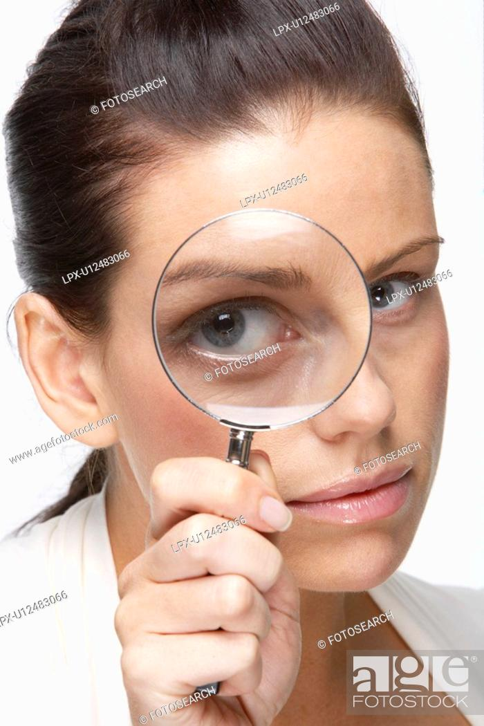 Stock Photo: Mid adult woman looking through magnifying glass.
